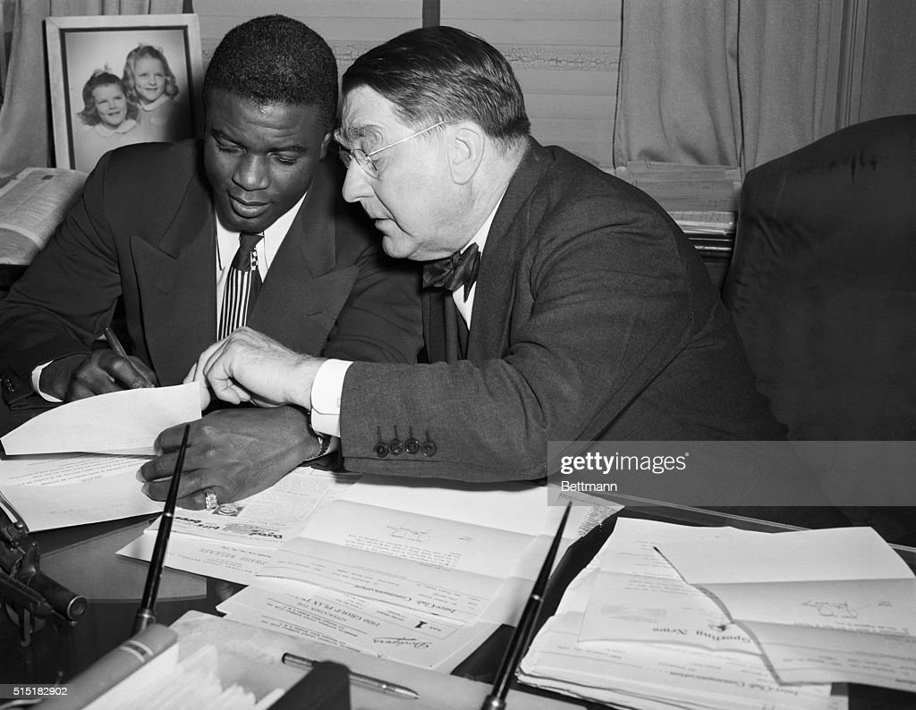 Jackie Robinson signs a contract with Brooklyn Dodger's team president Branch Rickey.