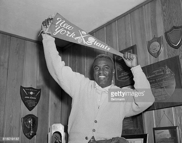 Jackie Robinson veteran Brooklyn Dodger ace holds aloft a New York Giant banner in his Stamford Connecticut home shortly after announcement today...