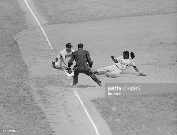 Jackie Robinson who knows all the angles slides safely into third to put the Brooklyns in scoring position in the second inning of the game against...