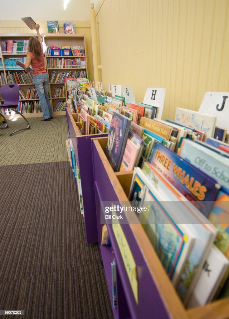 Jackie Sink, a Capitol Hill Cluster School parent volunteer, puts books on the shelves in the library at the Peabody Middle School on Monday, Oct. 22, 2007. The Peabody Middle School library has been refurbished with new furniture, carpets, air conditioning and bathrooms.