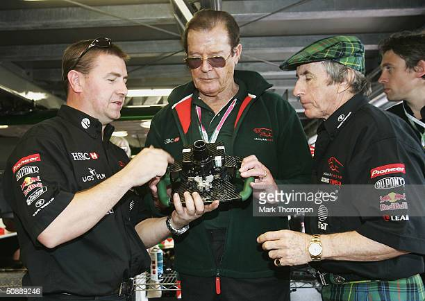 Jackie Stewart gives Roger Moore a guided tour of the Jaguar pit garage prior to the Monaco F1 Grand Prix on May 23 in Monte Carlo, Monaco.