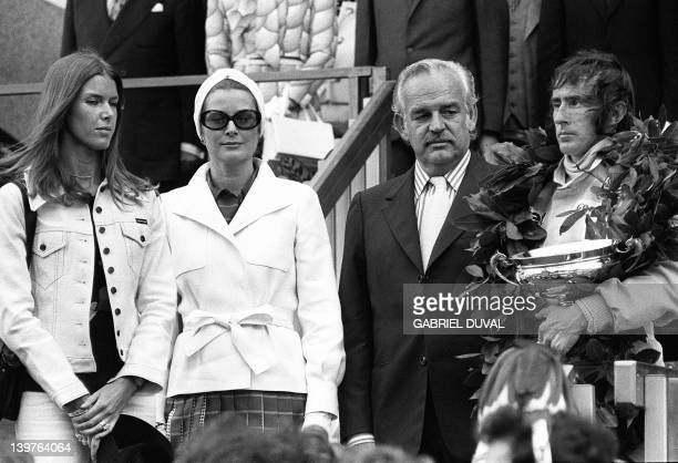 Jackie Stewart triple Formula One champion holds a trophy 04 June 1973 after he won the MonteCarlo grand prix while Prince Rainier III of Monaco his...