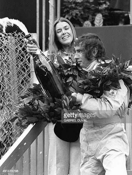 Jackie Stewart triple Formula One champion sprays champagne celebrating his victory in the MonteCarlo Formula Grand prix as his smiling wife looks on...