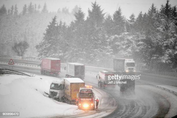 A jackknifed lorry is recovered on the M74 following motorists spending the night stranded on the motorway on January 17 2018 in Abington Scotland...