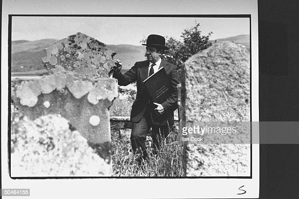 Jackofalltrades Seumas McSporran acting as registrar undertaker dressed formally in bowler hat checking out graves on tiny island one his many jobs...