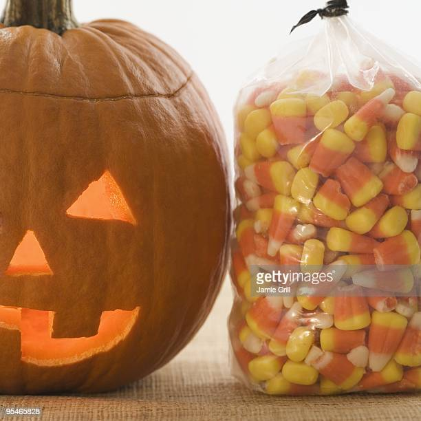 jack-o-lantern and bag of candy - candy corn stock photos and pictures