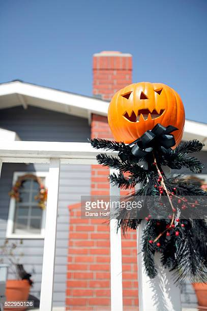 jack-o-lantern sitting on the post of a white fence - dana white stock pictures, royalty-free photos & images