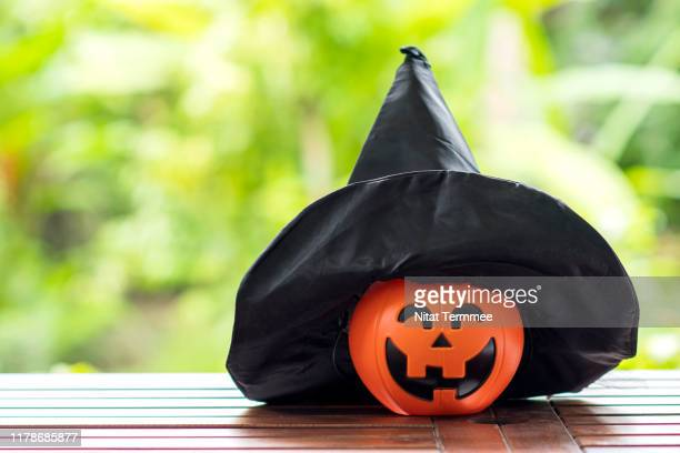 jack's head of a lantern pumpkin with black hat on wooden board. halloween decoration concepts. - ugly pumpkins stock photos and pictures