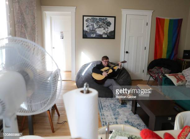 Jackson Barnett, a law student at Boston University and a classical pianist, plays guitar while self-isolating in his Allston apartment in Boston on...