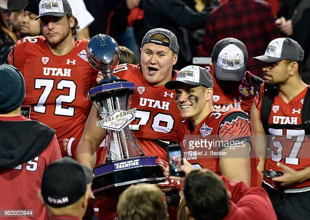 Jackson Barton and Cody Barton of the Utah Utes pose with a championship trophy after Utah defeated the Brigham Young Cougars, 35-28, at the Royal...