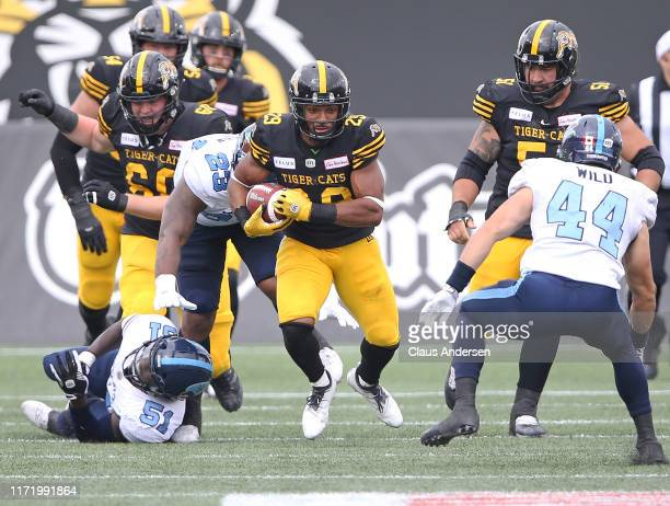 Jackson Bennett of the Hamilton Tiger-Cats runs the ball against the Toronto Argonauts during the annual Labour Day Classic at Tim Hortons Field on...