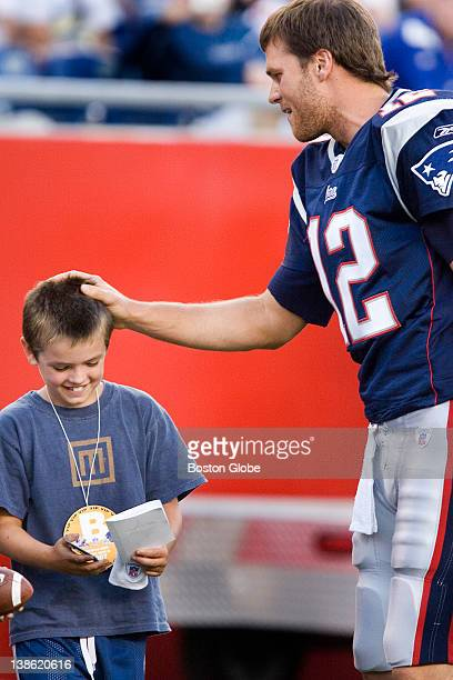 Jackson Damon nephew of actor Matt Damon, gets a pat on the head, an autograph and a wristband from patriots quarterback Tom Brady before the...
