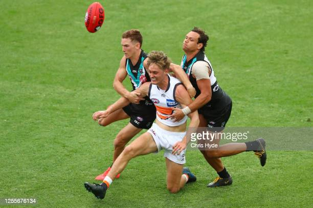 Jackson Hately of the Giants is tackled by Steven Motlop and Kane Farrell of the Power during the round 6 AFL match between the Port Adelaide Power...
