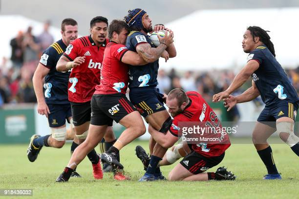Jackson Hemopo of the Highlanders tries to break the tackle of Ben Funnell and Oli Jager of the Crusaders during the Super Rugby trial match between...