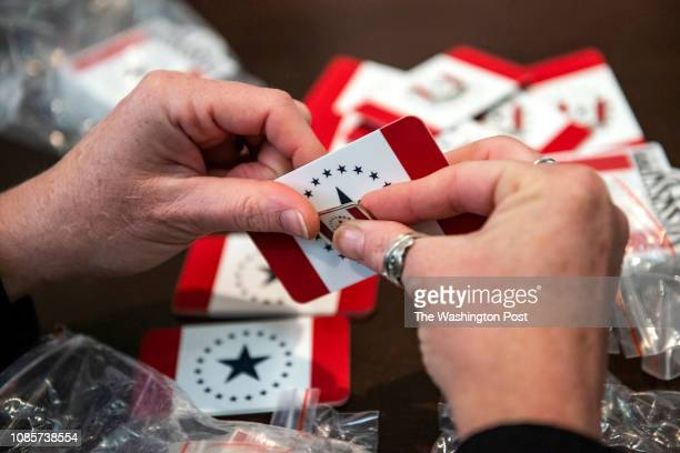 Laurin Stennis prepares lapel pins stickers and cards featuring her alternative design for the Mississippi state flag to hand out to attendees of the...