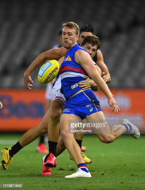 Jackson Macrae of the Bulldogs kicks whilst being tackled by Josh Thomas of the Magpies during the round 1 AFL match between the Western Bulldogs and...