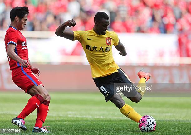 Jackson Martinez of Guangzhou Evergrande Taobao and Luo Xin of Chongqing Lifan vie for the ball during the first round match of CSL Chinese Football...