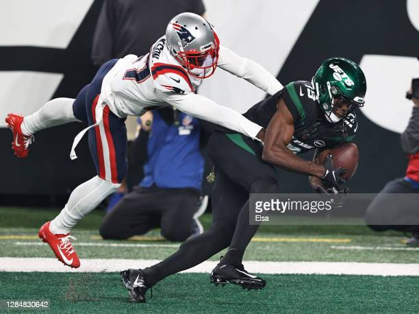 Jackson of the New England Patriots defends as Breshad Perriman of the New York Jets cannot hang on to the football during the first half at MetLife...