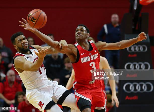 J Jackson of the Ohio State Buckeyes reaches past Souf Mensah of the Rutgers Scarlet Knights for a loose ball during the second half of a game at...