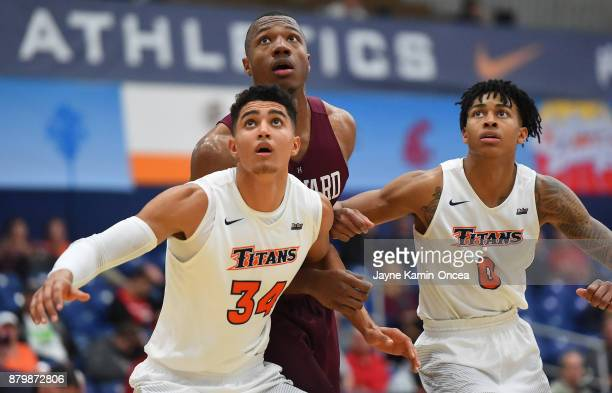 Jackson Rowe and Kyle Allman of the Cal State Fullerton Titans and Chris Lewis of the Harvard Crimson wait for a rebound at the Titan Gym on November...