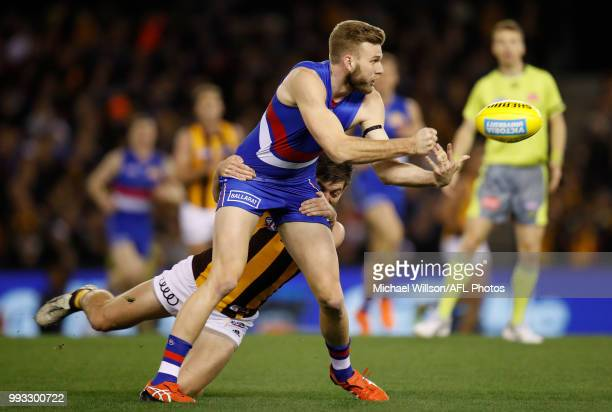 Jackson Trengove of the Bulldogs is tackled by Ricky Henderson of the Hawks during the 2018 AFL round 16 match between the Western Bulldogs and the...