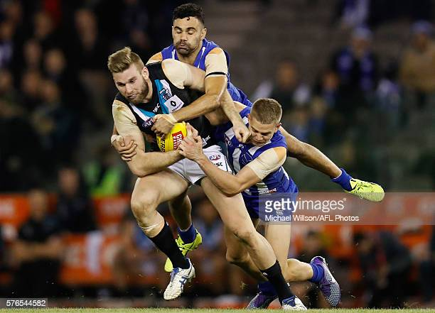 Jackson Trengove of the Power is tackled by Lindsay Thomas and Jed Anderson of the Kangaroos during the 2016 AFL Round 17 match between the North...
