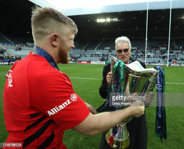 Jackson Wray of Saracens passes the trophy to Saracens owner Nigel Wray during the Champions Cup Final match between Saracens and Leinster at St...
