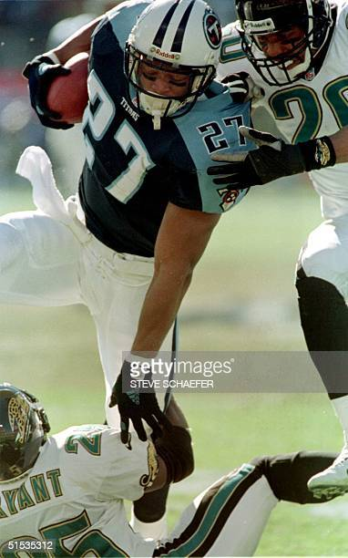 Jacksonville Jaguar's Fernando Bryant and Donovin Darius try and bring down Tennessee Titans' runningback Eddie George during a first half run during...