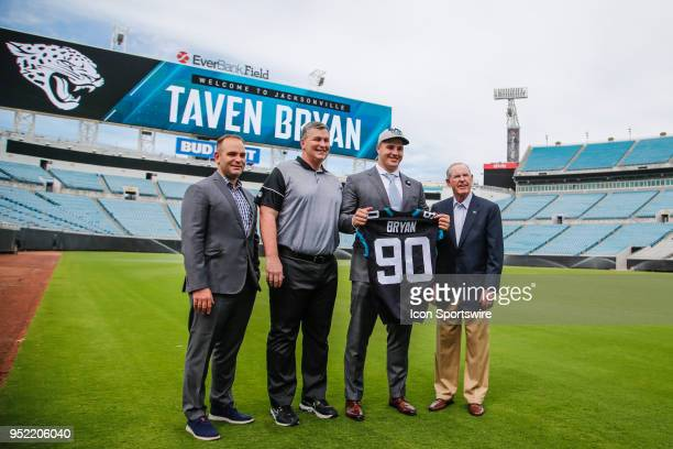Jacksonville Jaguars first round draft pick Taven Bryan shows off his new jersey while addressing the media along with from left to right general...