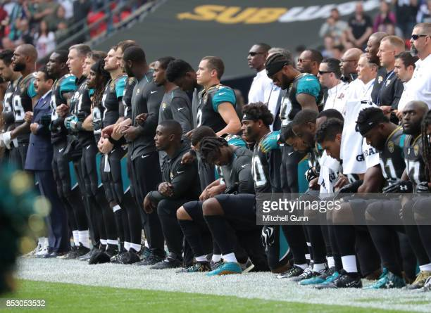 Jacksonville Jaguars Owner Shahid Kahn links arms with his team as some players take a knee during the National Anthem during the NFL match between...