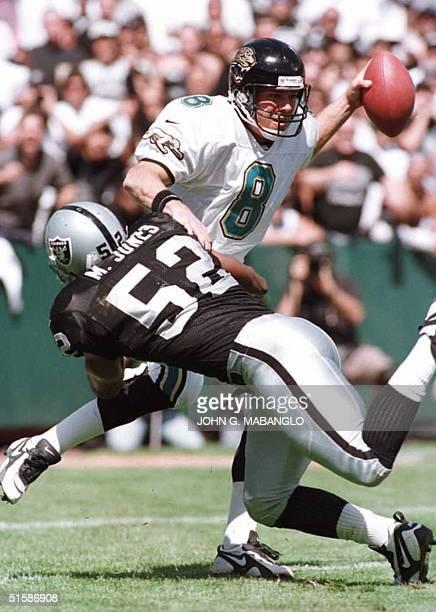 Jacksonville Jaguars quarterback Mark Brunell gets pressured by Oakland Raiders linebacker Mike Jones during their 15 September game in Oakland,...