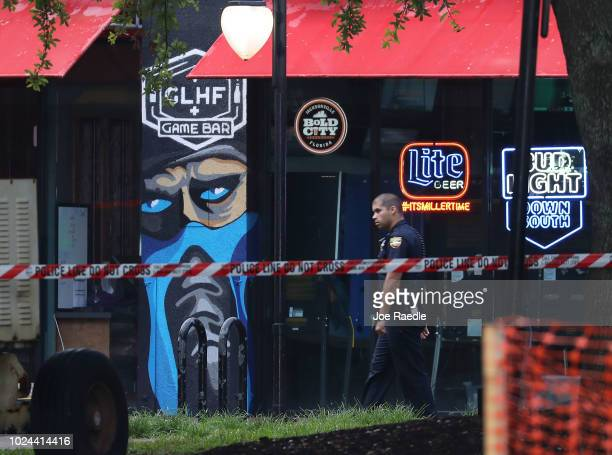 Jacksonville Sheriff officer walks past the GLHF Game Bar where 3 people including the gunman were killed at the Jacksonville Landing on August 27...