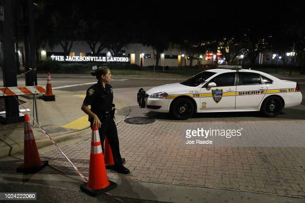 Jacksonville Sheriff's officer helps keep the perimeter secure as law enforcement investigates a shooting at the GLHF Game Bar which uses the same...