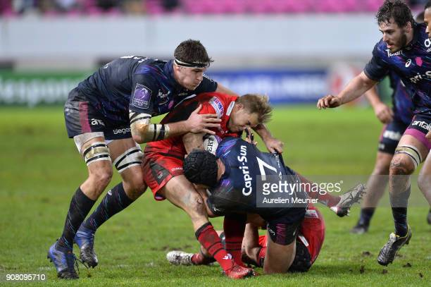 Jaco Van Der Walt of Edinburgh is tackled by Mathieu Ugane and Alexandre Flanquart of Stade Francais during the European Rugby Challenge Cup match...
