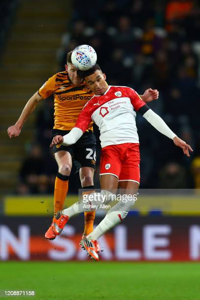 Jacob Brown of Barnsley FC wins the header from Callum Elder of Hull City during the Sky Bet Championship match between Hull City and Barnsley at...