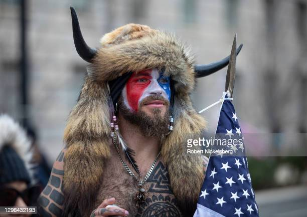 """Jacob Chansley, a.k.a. Jake Angeli and the QAnon Shaman, speaks to passersby during the """"Stop the Steal"""" rally on January 06, 2021 in Washington, DC...."""
