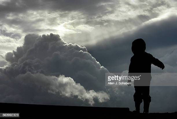 Jacob Collier of Long Beach bird watches with his father Timothy Collier as the sun breaks through storm clouds rolling by in the sky over Bolsa...