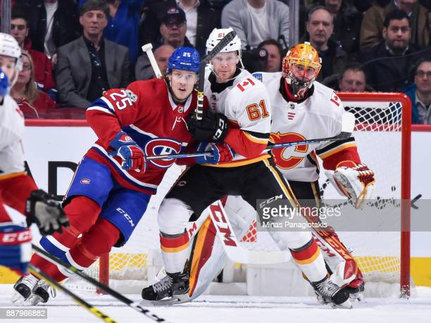 Jacob de la Rose of the Montreal Canadiens and Brett Kulak of the Calgary Flames battle for position in front of goaltender David Rittich during the...