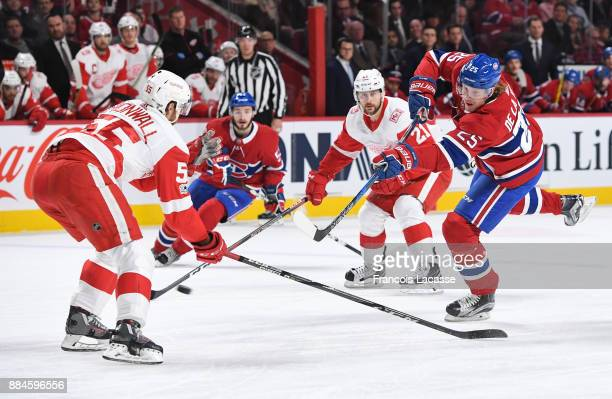 Jacob De La Rose of the Montreal Canadiens fires a shot in front of Niklas Kronwall of the Detroit Red Wings in the NHL game at the Bell Centre on...