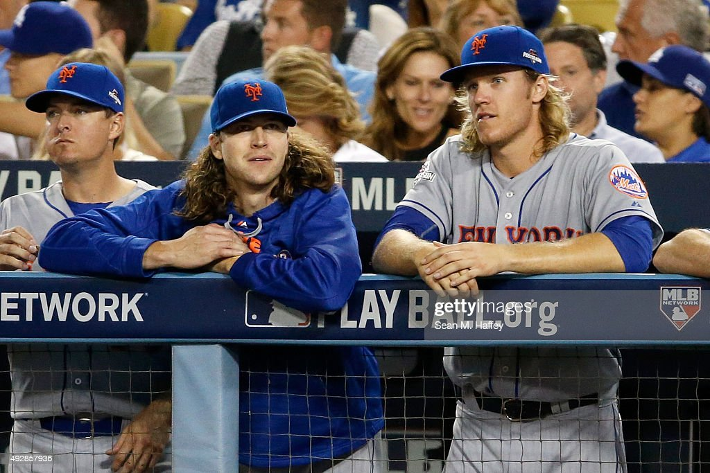 Jacob deGrom #48 and Noah Syndergaard #34 of the New York Mets watch from the dugout in the eighth inning against the Los Angeles Dodgers in game five of the National League Division Series at Dodger Stadium on October 15, 2015 in Los Angeles, California.