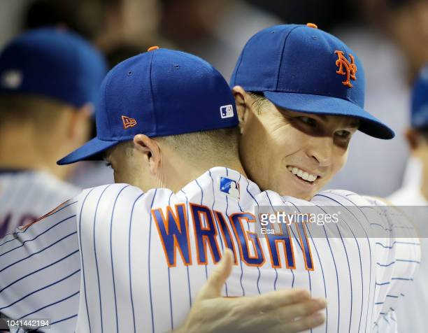 Jacob deGrom of the New York Mets is congratulated by teammate David Wright as deGrom walked into the dugout after the final out of the eighth inning...