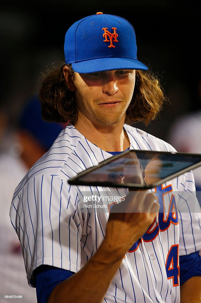Jacob deGrom #48 of the New York Mets spins a tablet on his finger in the dugout during a game against the Colorado Rockies at Citi Field on July 29, 2016 in the Flushing neighborhood of the Queens borough of New York City.
