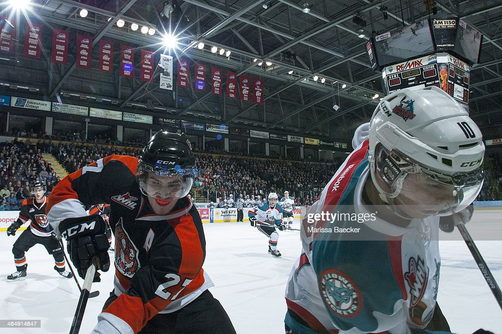 Jacob Doty #28 of the Medicine Hat Tigers checks Nick Merkley #10 of the Kelowna Rockets at the boards on January 24, 2014 at Prospera Place in Kelowna, British Columbia, Canada.