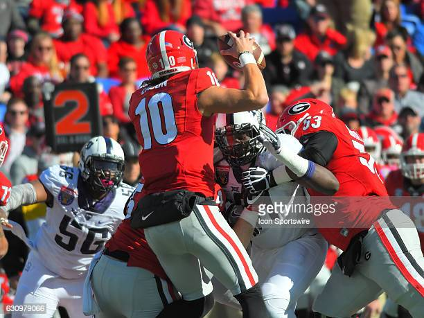 Jacob Eason Georgia Bulldogs quarterback tries to avoid the pressure being applied by LJ Collier TCU Horned Frogs defensive linemen as Brandon...