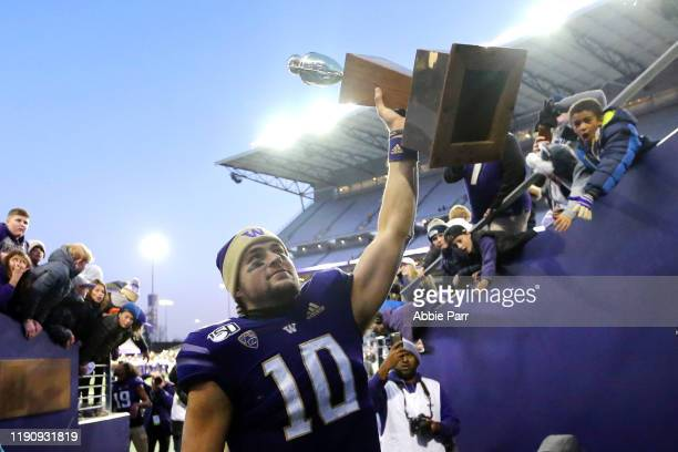 Jacob Eason of the Washington Huskies holds the Apple Cup trophy while walking to the locker room after defeating the Washington State Cougars 3113...