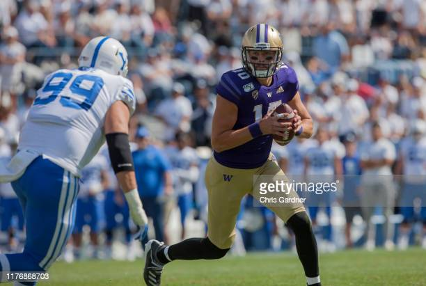 Jacob Eason of the Washington Huskies rolls out of the pocket looking for an open receiver against the BYU Cougars at LaVell Edwards Stadium on...