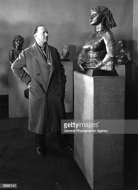 Jacob Epstein Americanborn British sculptor examining his work 'Isobel' at the exhibition held at the Lancaster Galleries London