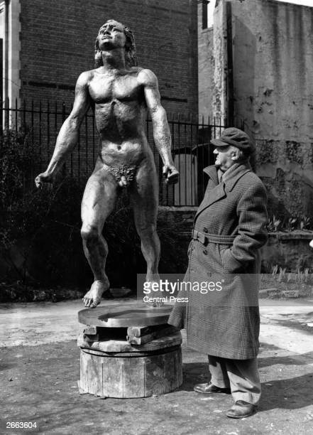 Jacob Epstein Americanborn British sculptor looking at his finished bronze statue 'Youth Advancing' which will be on show at the Festival of Britain...