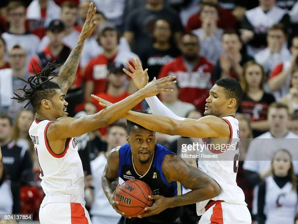 Jacob Evans and Kyle Washington of the Cincinnati Bearcats defend Martins Igbanu of the Tulsa Golden Hurricane during the first half at BB&T Arena on...