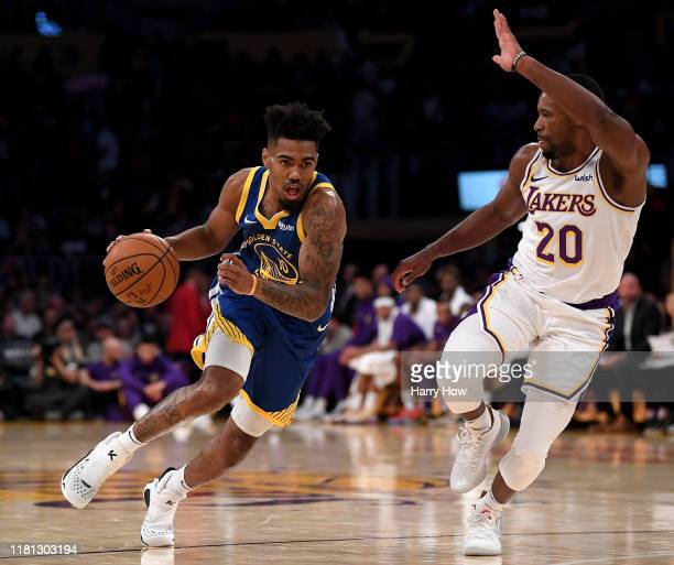Jacob Evans of the Golden State Warriors drives to the basket on Demetrius Jackson of the Los Angeles Lakers during a 104-98 Lakers preseason win...